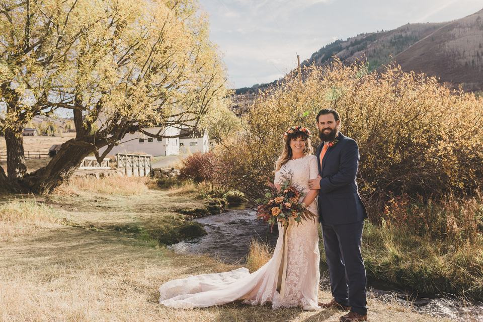 bride and groom pose by pond during Park City elopement