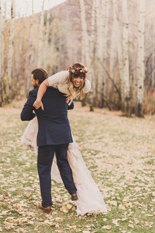groom lifts bride up over shoulder during UT wedding photos