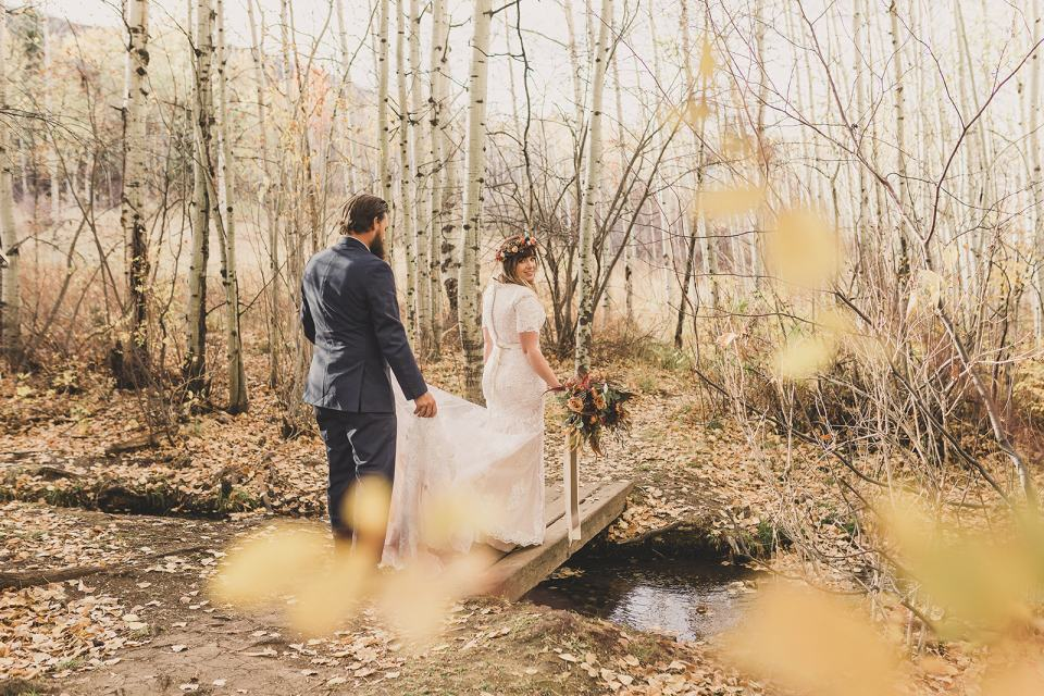 groom lifts bride's gown while walking through woods