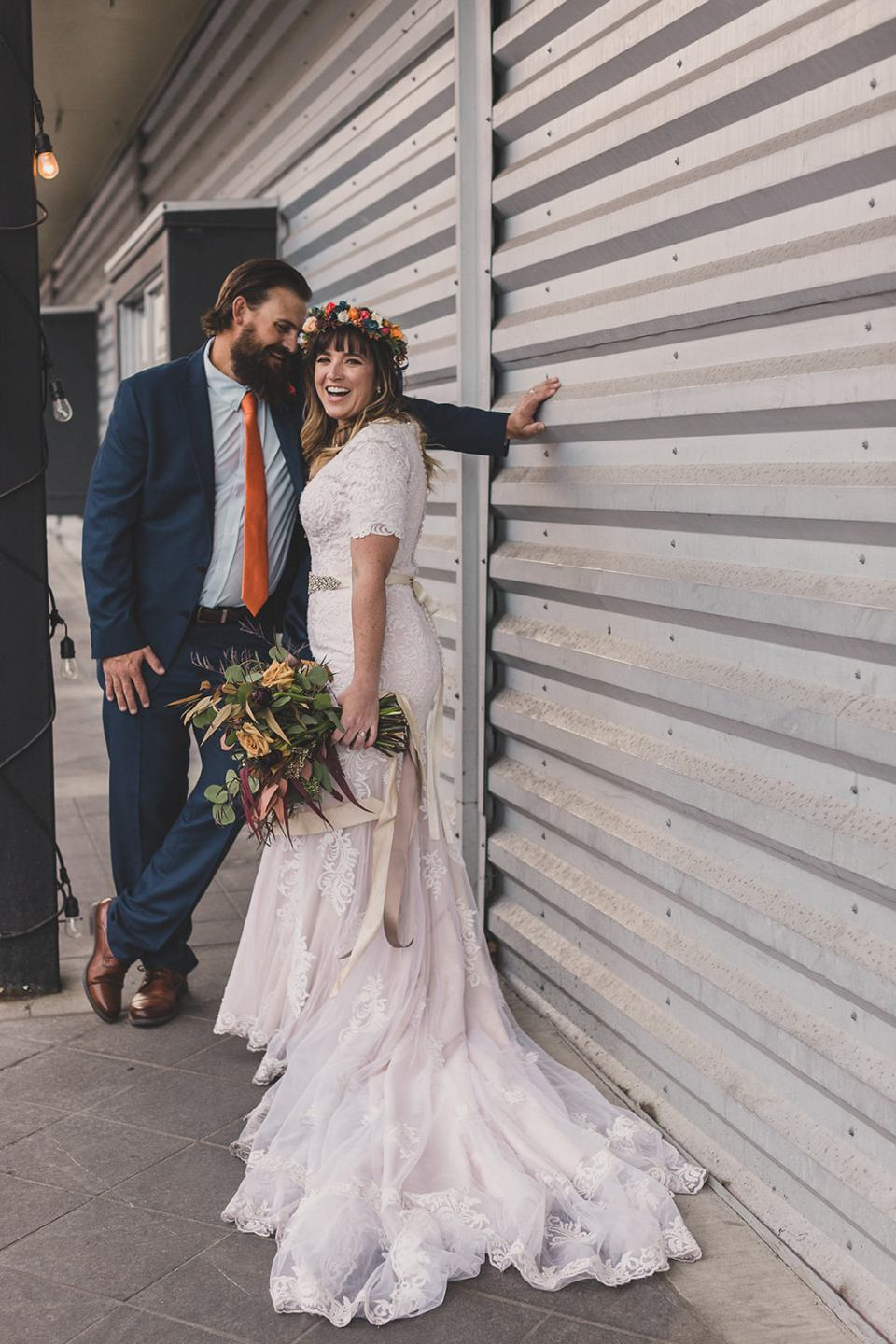 bride and groom pose by side of building in Park CIty