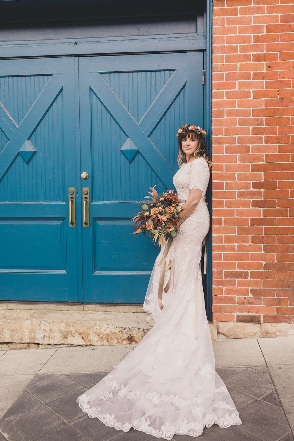 bride poses against brick wall by blue gate