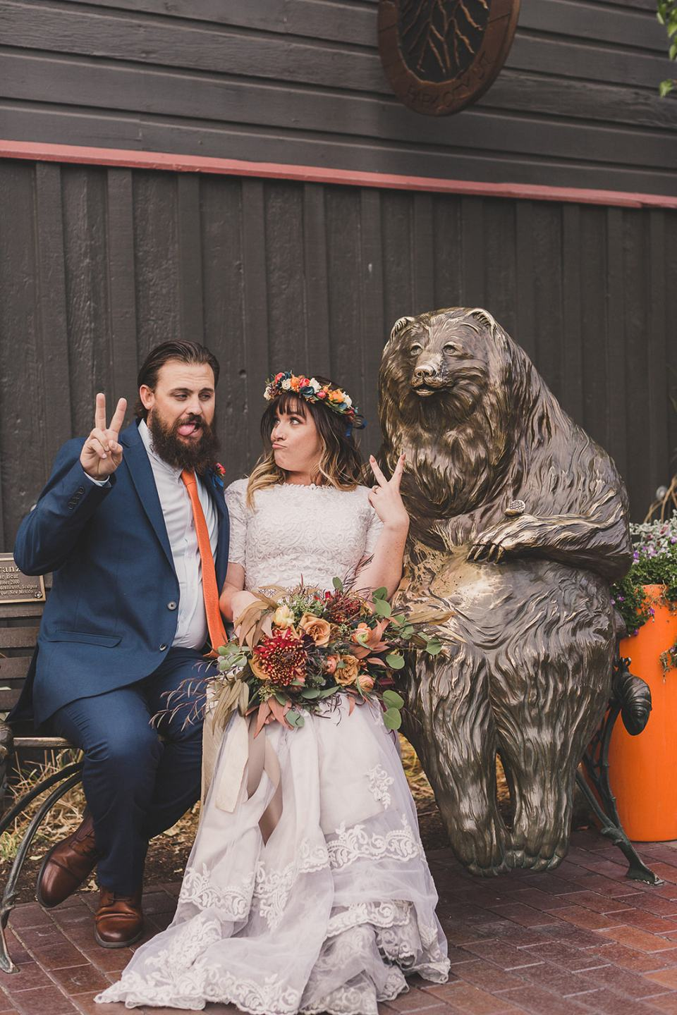 newlyweds pose with bear statue