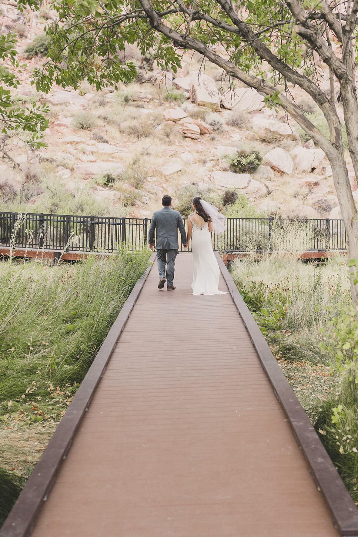 newlyweds walk on boardwalk after Red Spring Boardwalk Elopement