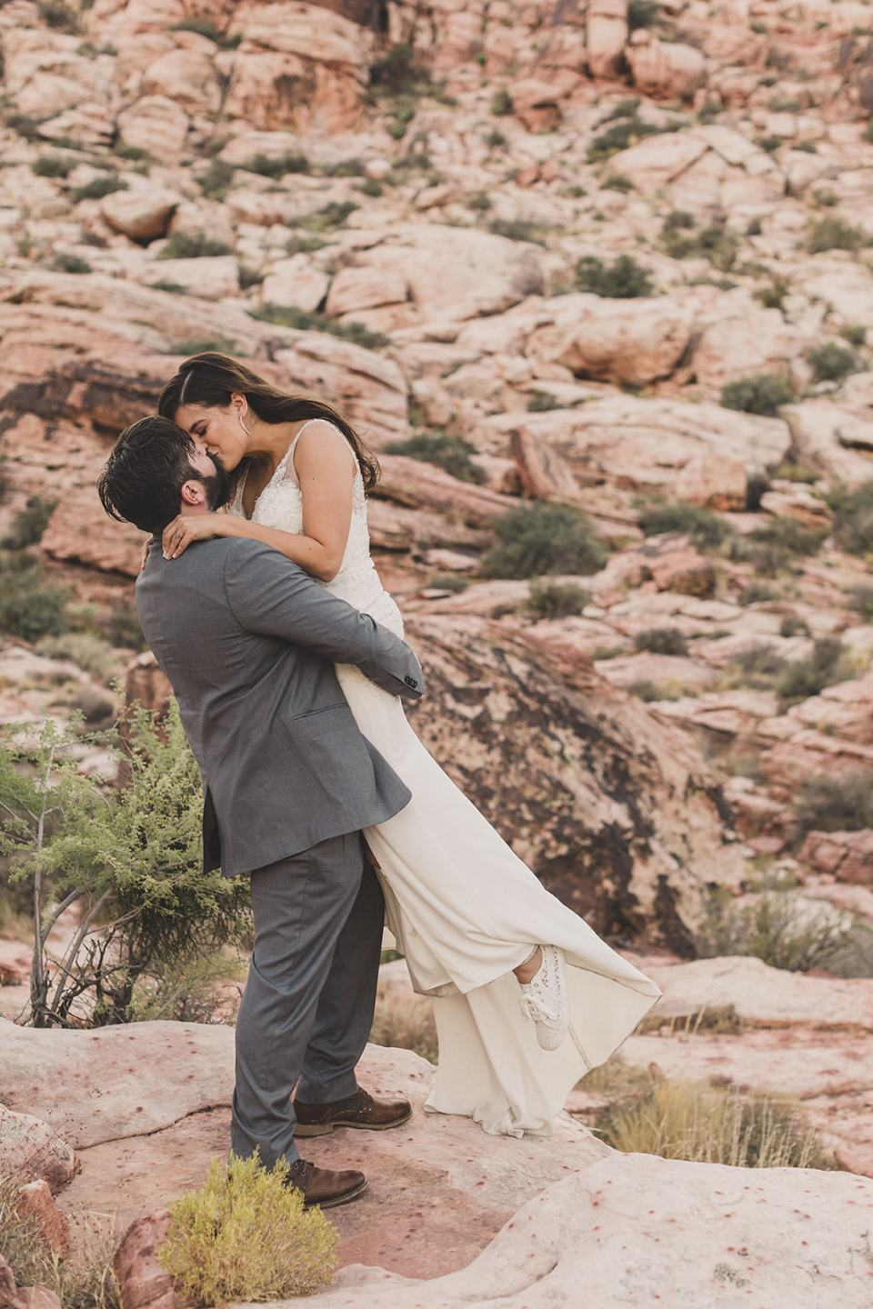 groom picks up bride in Red Rock Canyon
