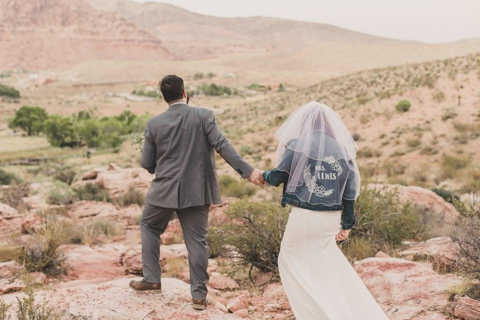 groom leads bride in custom jacket over rocks