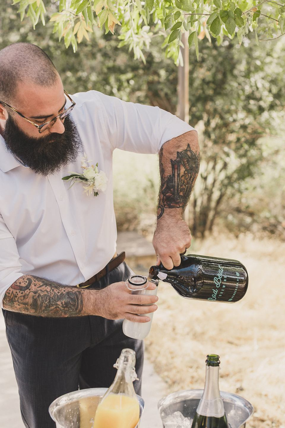 groom pours champagne for toast