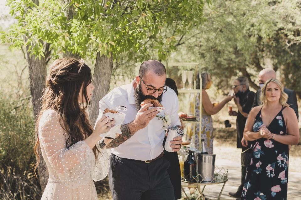 newlyweds eat donuts with wedding guests