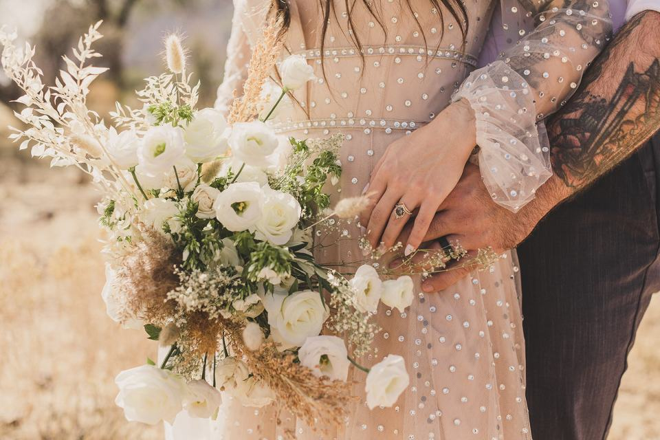 bride and groom hold hands by bouquet