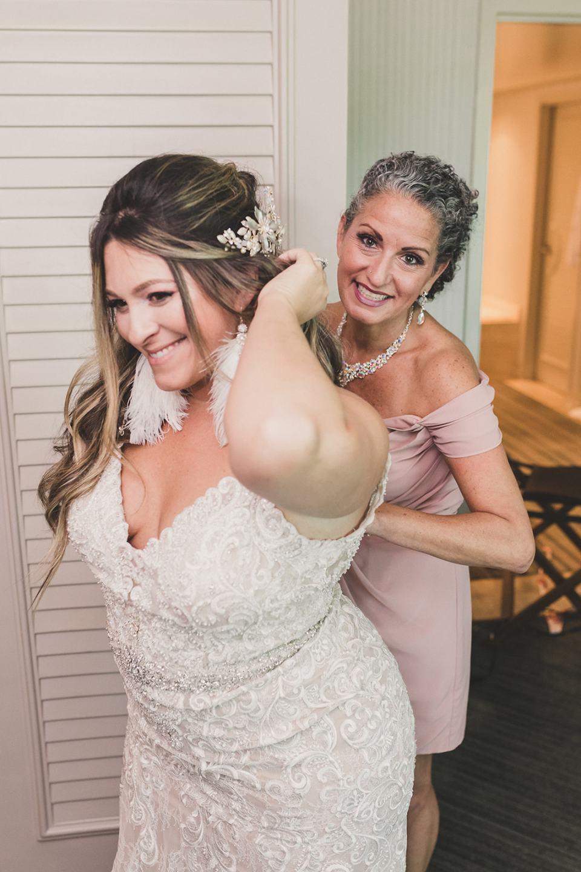 bridesmaid helps bride with wedding dress