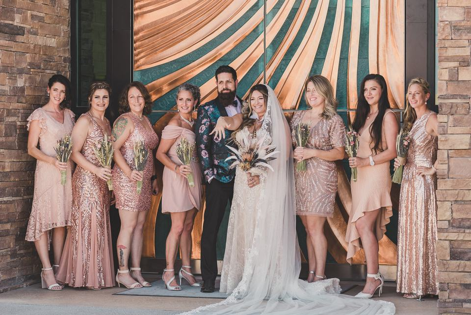 bride and groom pose with bridesmaids in pink gowns
