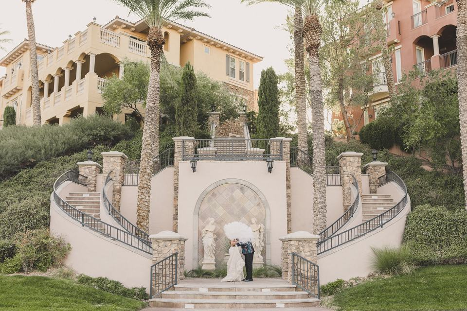bride and groom pose on staircase at The Westin Lake Las Vegas