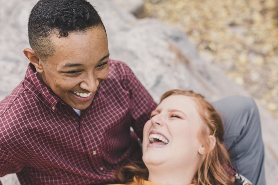 couple laughs while sitting on rocks in Mt Charleston