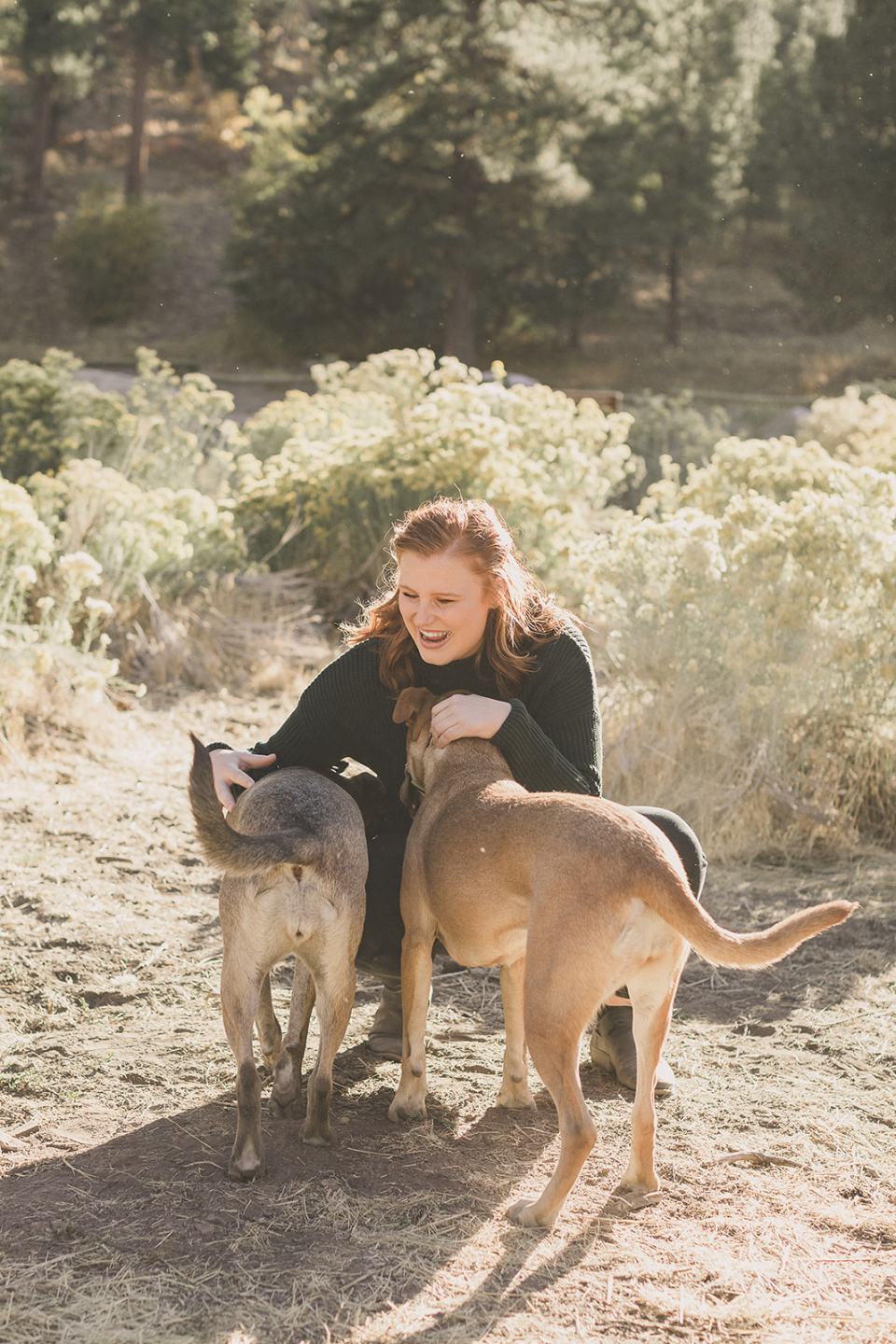 mom plays with two dogs during family photos