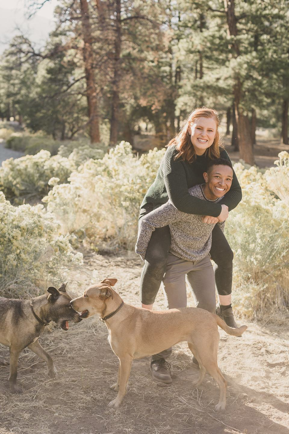 couple gives piggy back ride while dogs play