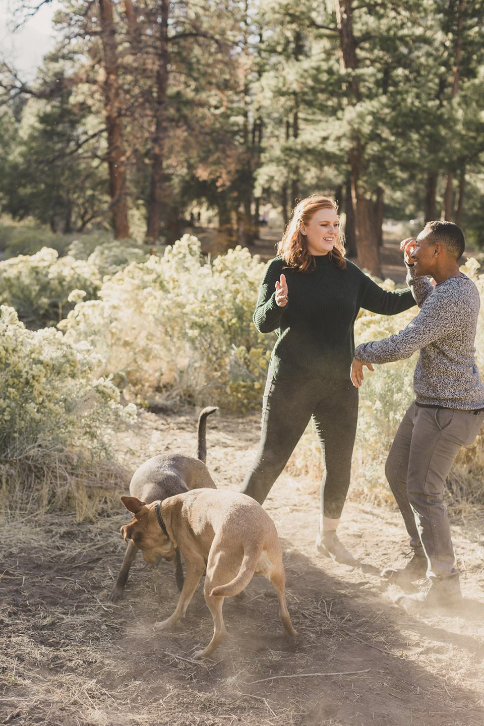 couple walks along trail along Mt Charleston with dogs playing