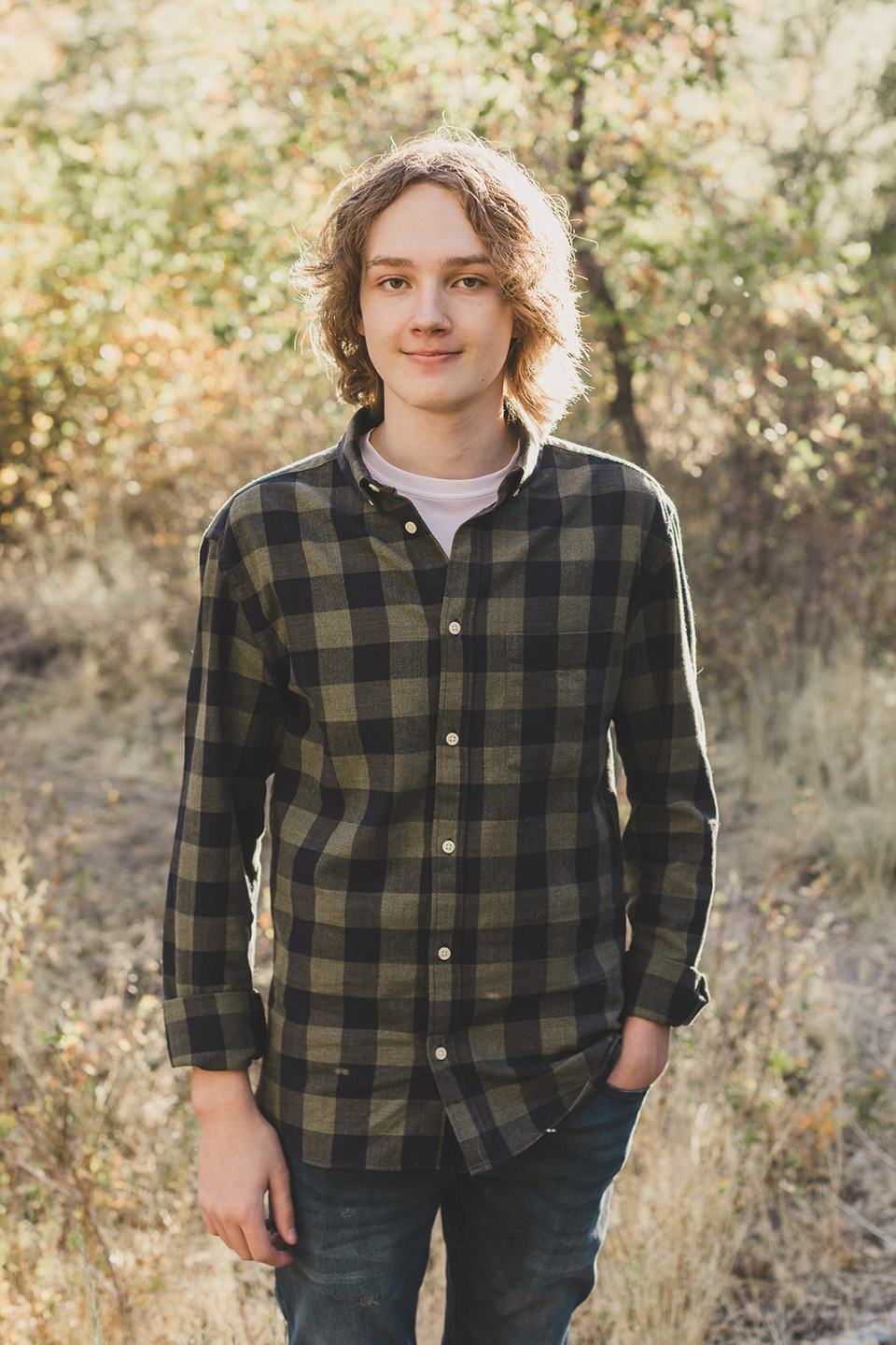 son in green plaid shirt poses during Mt Charleston Family Portraits