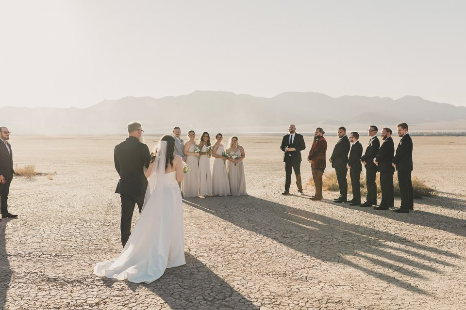 bride walks to ceremony in desert with dad