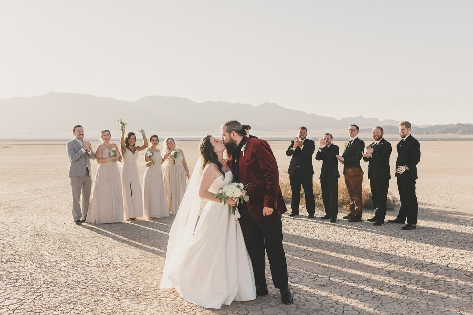 bride and groom kiss with bridal party behind them in desert