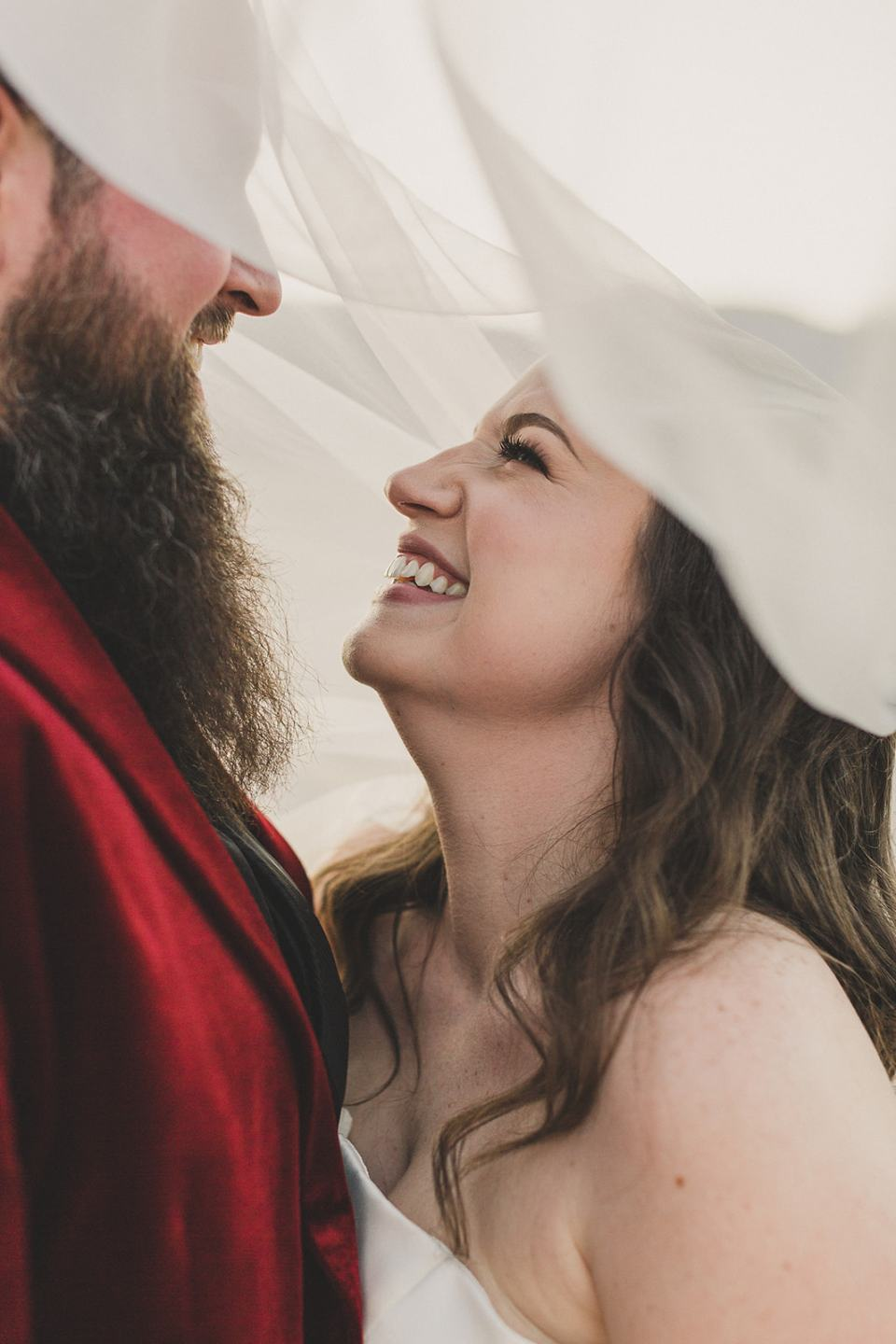 newlyweds laugh under bride's veil during wedding portraits in desert