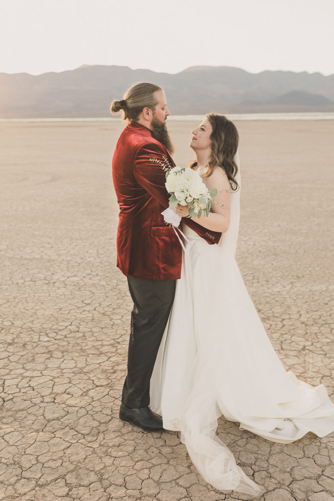 bride and groom talk in desert during wedding portraits