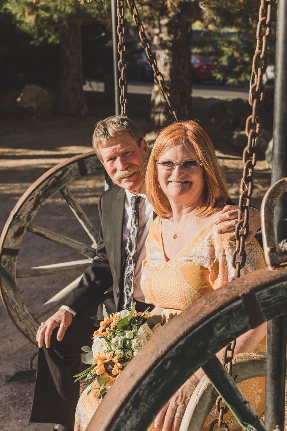 bride in yellow dress sits on wooden wheel with groom