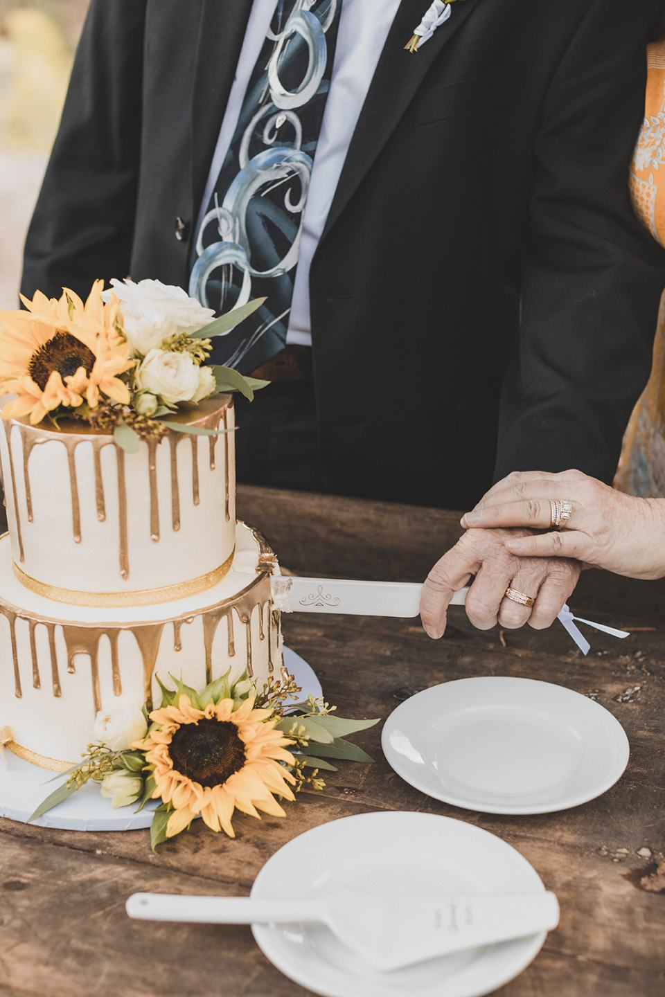 newlyweds cut wedding cake with gold drip and sunflowers