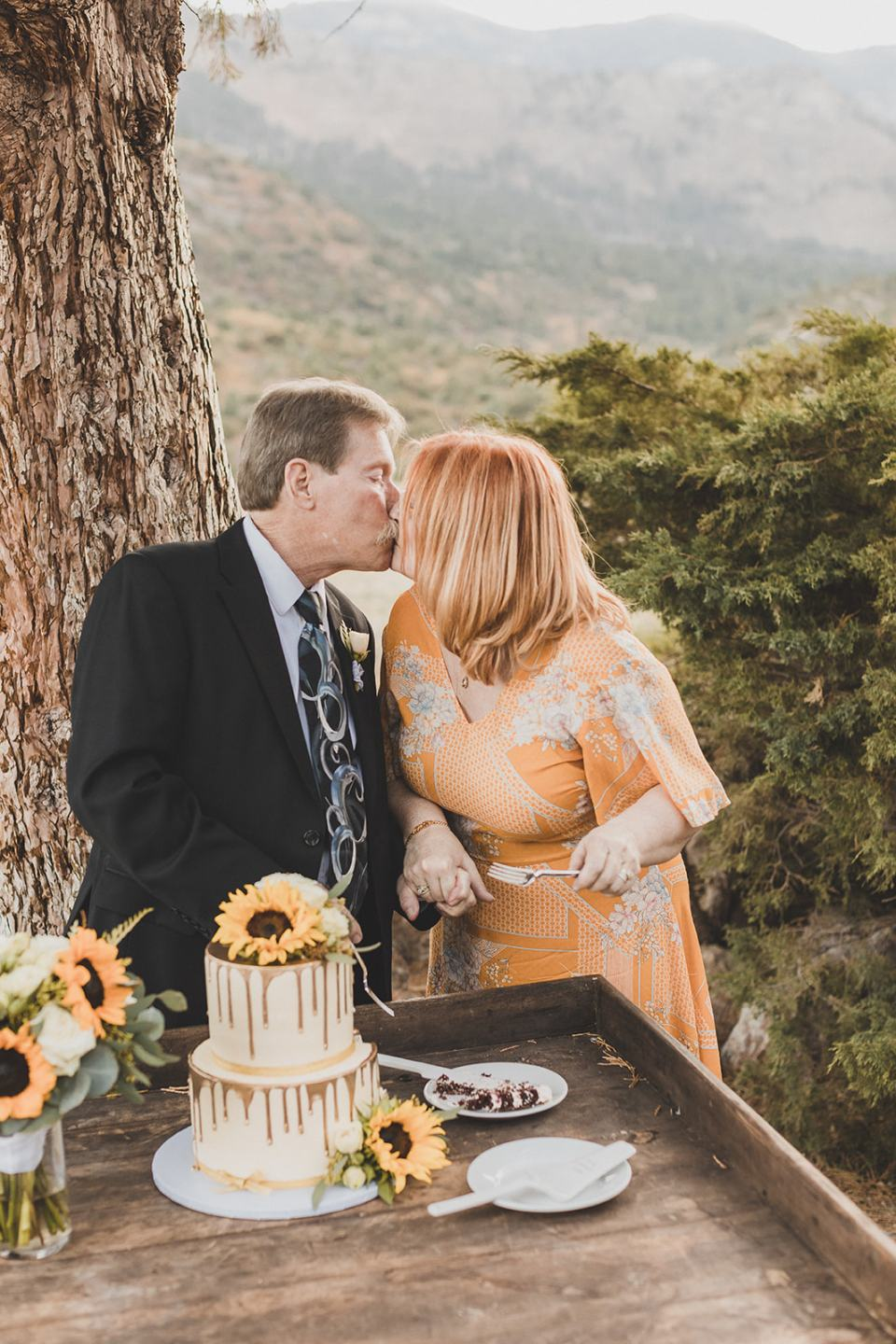newlyweds cut wedding cake with sunflower topper