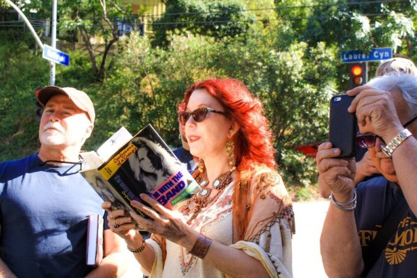 """People listen to Pamela as she reads from her book """"I'm With the Band"""" at a location in Laurel Canyon"""