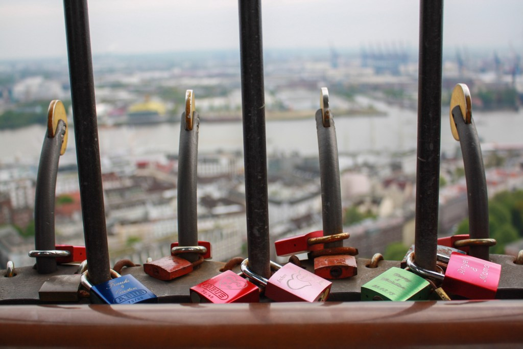 Keychains on wrought iron bars overlooking the city of Hamburg, Germany