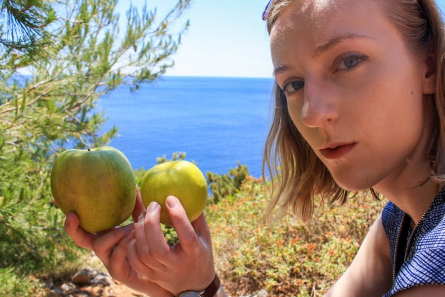 A woman holds two apples while on the trail to Odysseus Cave, Mljet Island Croatia