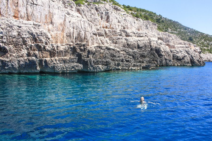 A woman swimming in the water at Odysseus Cave, Mljet Island Croatia