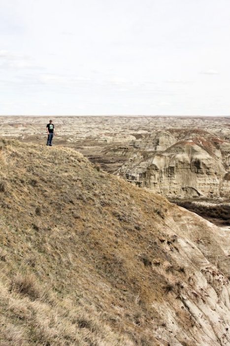 A man stands on a cliff's edge at dinosaur provincial park in Alberta, Canada