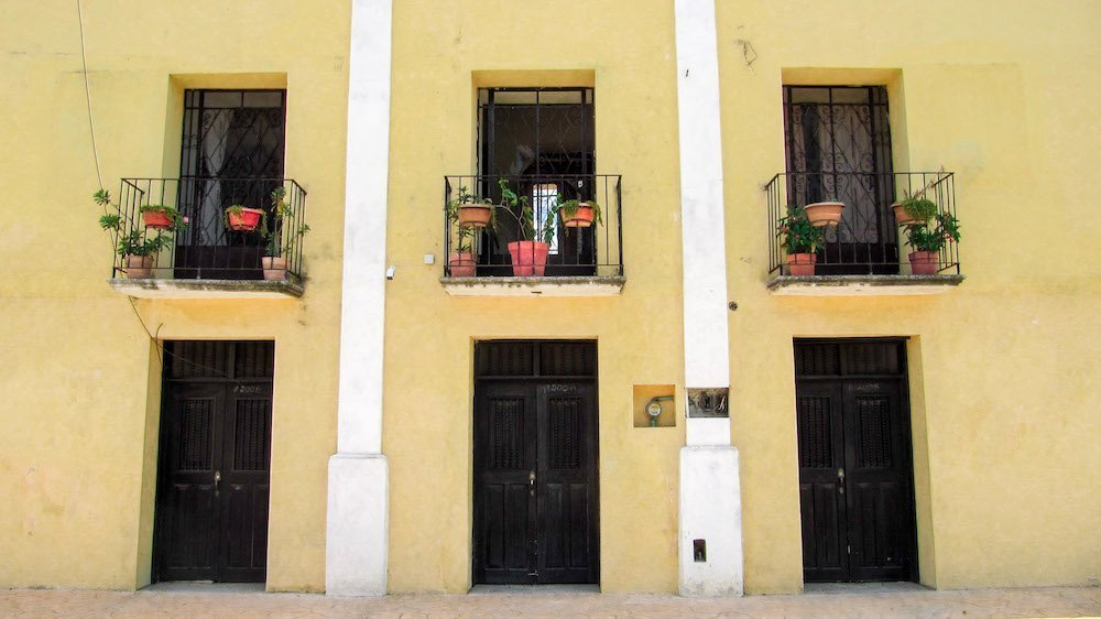 A symmetrical, yellow building with flowers in Valladolid, Mexico