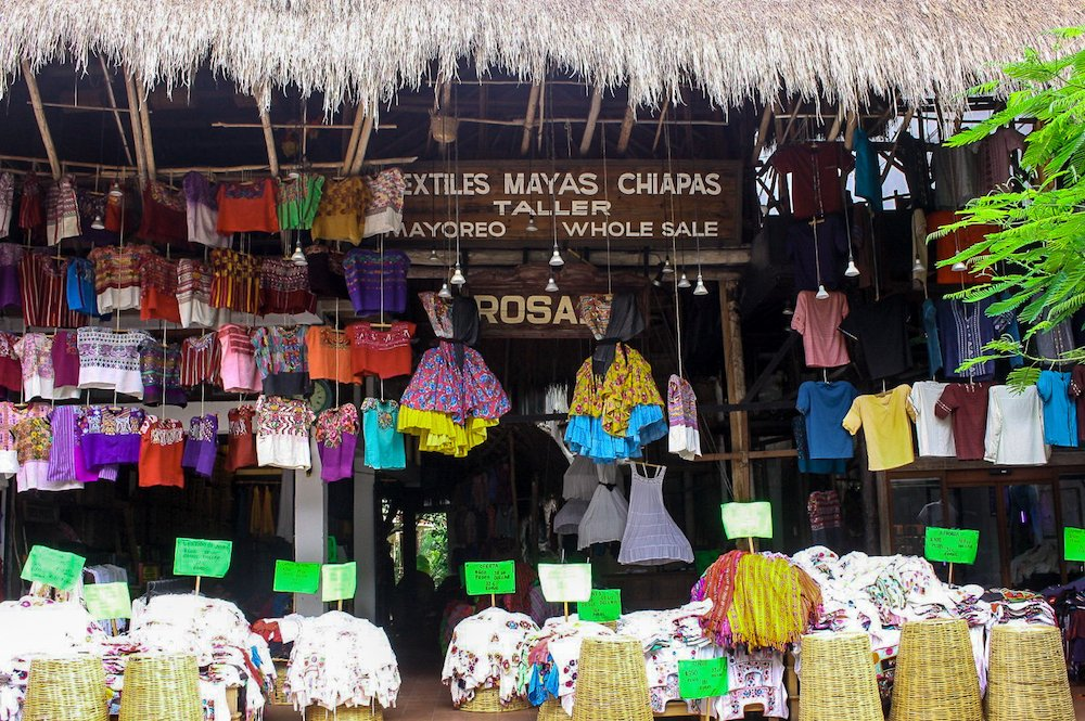 A traditional clothing store in playa del carmen with mounds of clothing on display