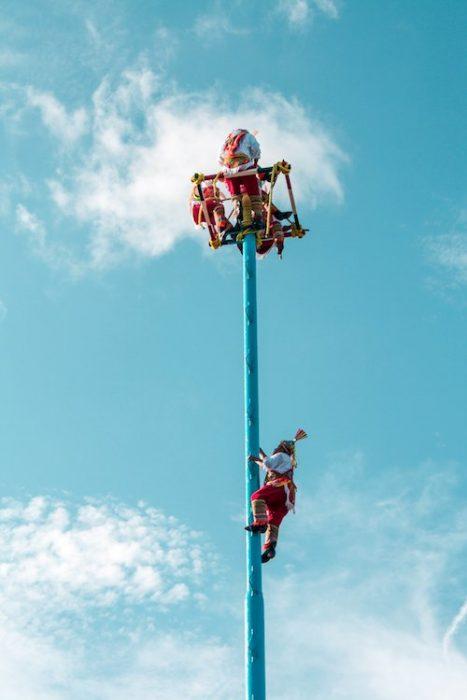 Five men do a mayan raindance atop a tall pole in playa del carmen, Mexico