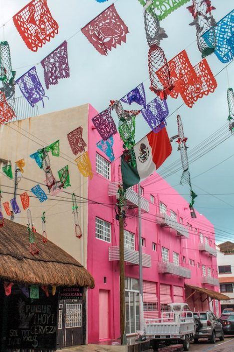 A pink building and Mexico flags in downtown playa del Carmen