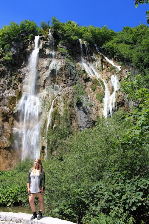 Taylor standing in front of a tall waterfall at Plitvice National Park in Croatia