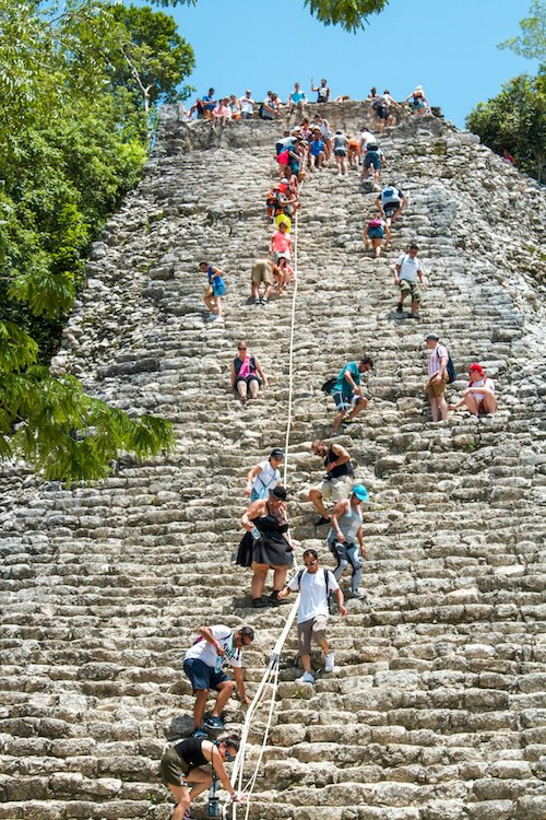 Many people climbing the Nohoch Mul pyramid at coba ruins in quintana roo, mexico