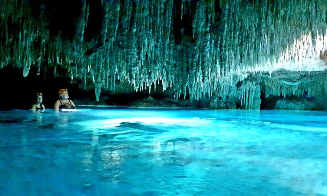 Two women stand in bright blue water under stalactites in a cave near Tulum, Mexico