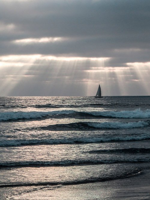 A sailboat rests on the waters offshore in Oceanside California
