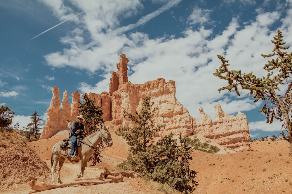 A man rides a horse in front of hoodoos in Bryce Canyon National Park, Utah