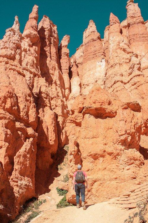A man walks along a trail among red rock hoodoos in Bryce Canyon National Park, Utah