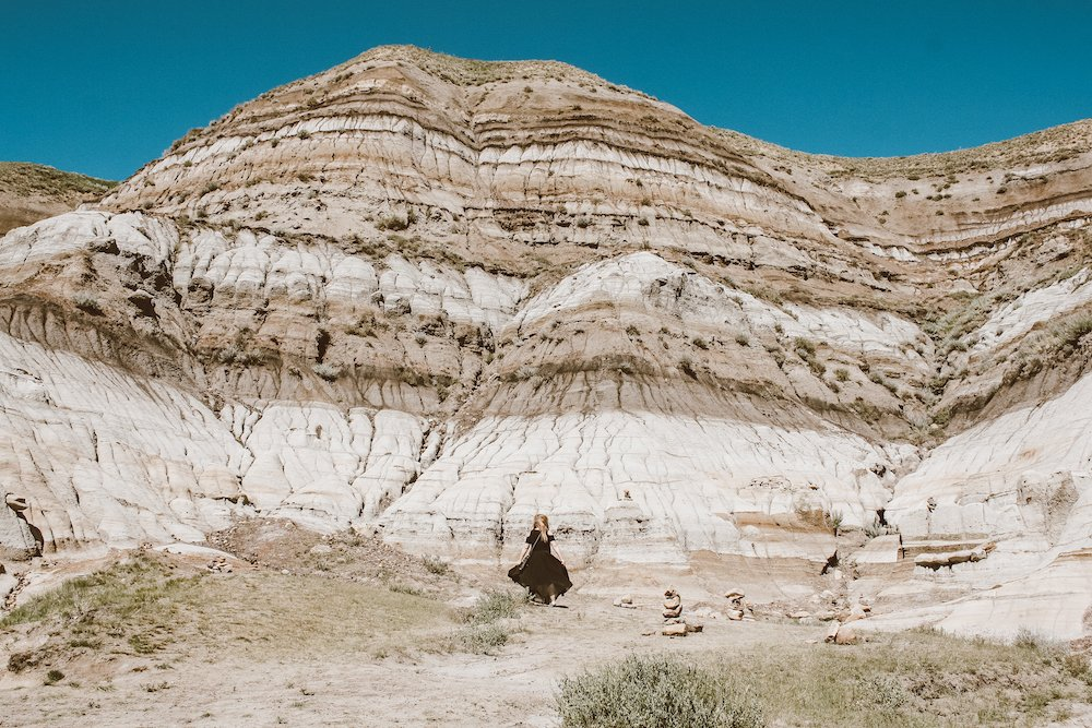 Taylor stands in front of layered, exposed, sandstone rock in Drumheller Alberta in the summer