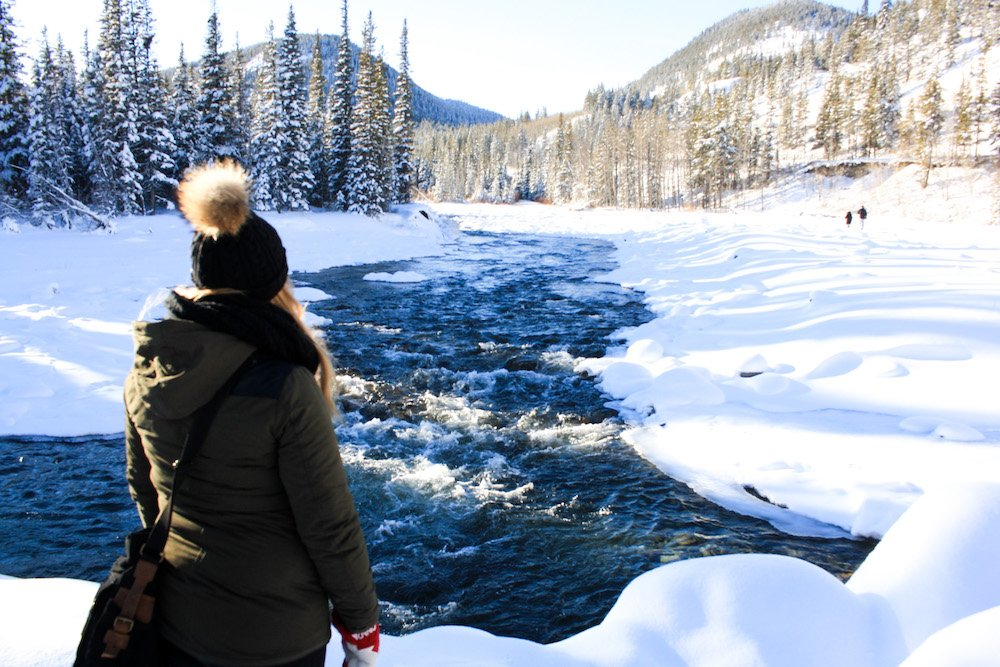 Taylor stands among a rushing river and fluffy white snow in Kananaskis Alberta
