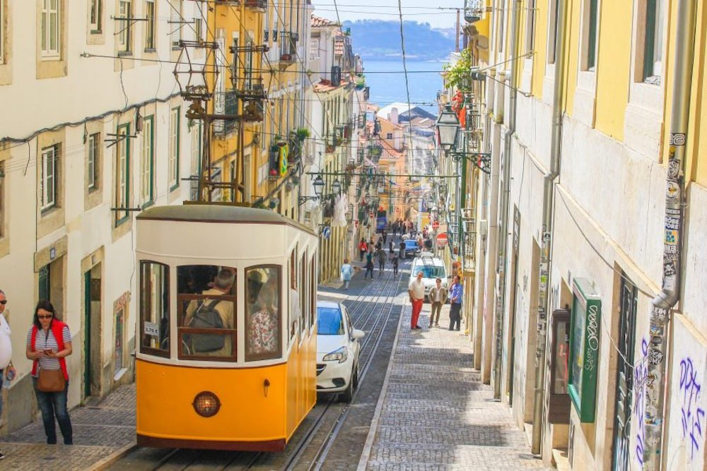 An orange trolley rides up the rails on a busy street in Lisbon, Portugal