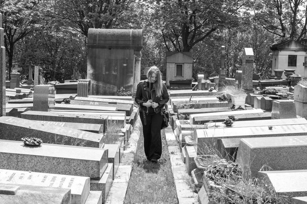 Me walking among graves in Pere Lachaise Cemetery in Paris France, black and white