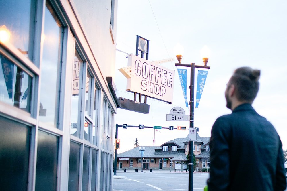 A man stands in front of a coffee shop in Red Deer, Alberta, Canada
