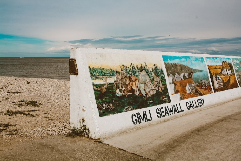 Gimli seawall gallery sign with the lake and beach in the background