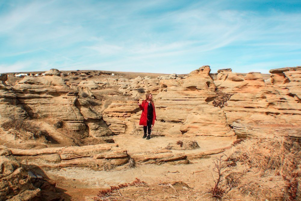 Taylor stands among red rocks and hoodoos in Writing on stone provincial park in Alberta Canada