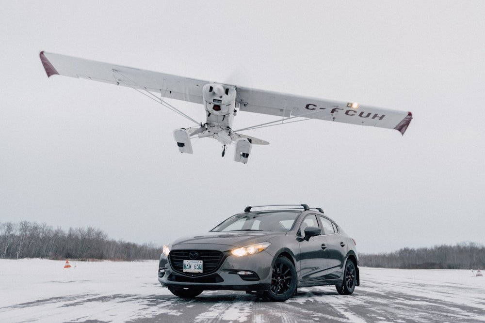 A car on ice with a small plane overhead in Gimli, Manitoba